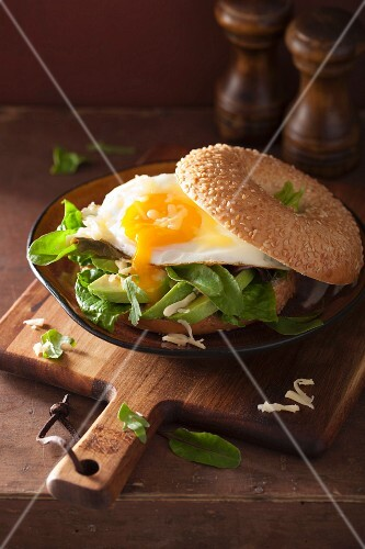 A breakfast bagel with a fried egg, avocado and cheese