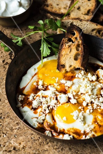 Fried eggs in garlic yoghurt with grilled bread