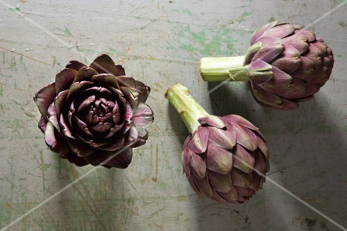 Three artichokes on a rustic surface