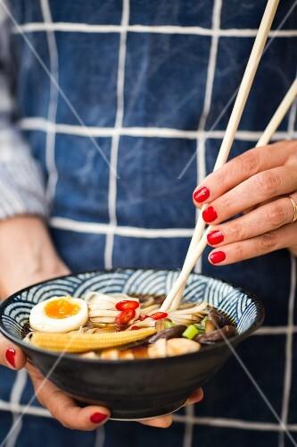 A woman's hands holding a bowl of ramen soup