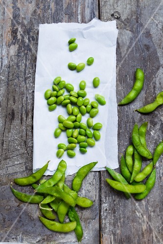 Edamame beans on a piece of paper and on a wooden surface