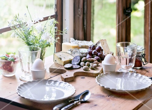 Breakfast with soft-boiled eggs, grapes, jam, salami, cheese and caprese salad