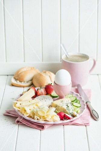 Cheese breakfast with an egg, radishes, strawberries, cucumber, bread rolls and coffee