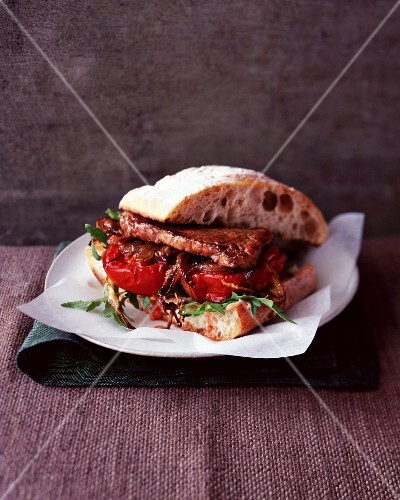 A steak sandwich with tomatoes and rocket