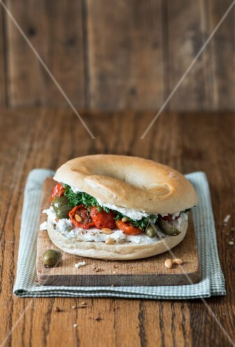 A bagel with dried tomatoes, caper fruits, pine nuts and goats' cheese
