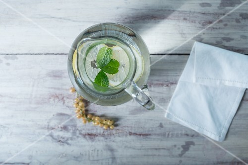 A glass water jug with lemon and mint on a white wooden surface next to whitecurrants and a fabric napkin