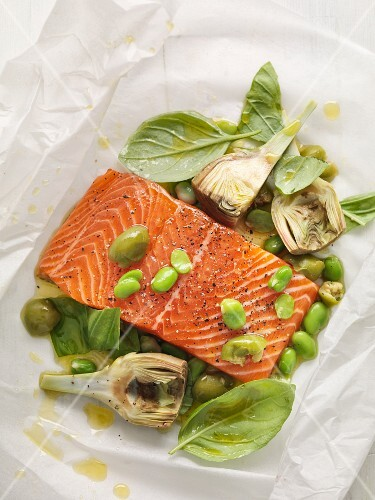Salmon fillet with artichokes, olives and basil on parchment paper