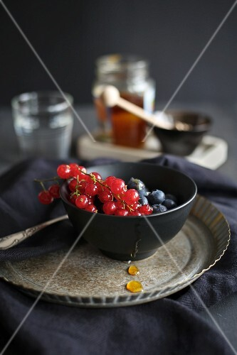 Fresh berries with honey in a dark bowl