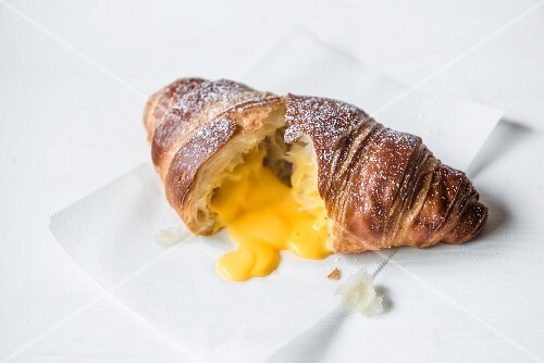 A croissant filled with salted egg yolk cut open on a baking parchment