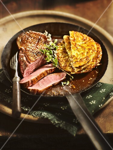 Medium duck breast with red wine sauce and potato fritters