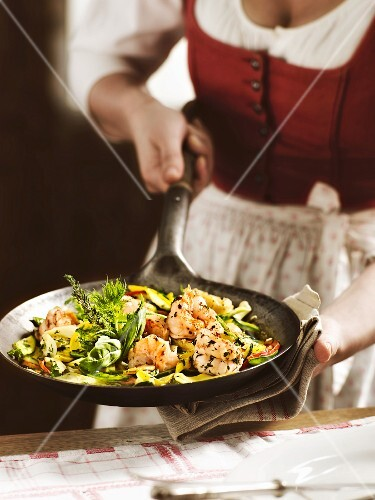 A woman in a traditional dirndl dress serving a dish of giant prawns with herbs