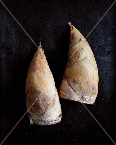 Two unpeeled bamboo shoots on a black surface