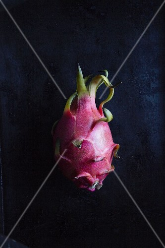 A pitahaya (dragon fruit) on a black surface
