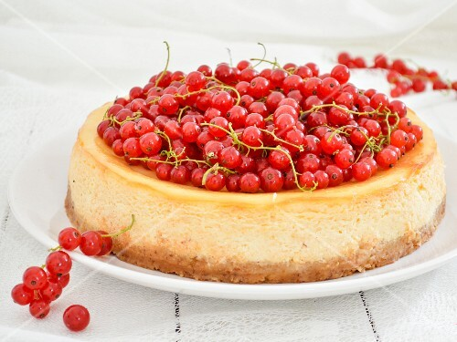 A cheesecake topped with fresh redcurrants