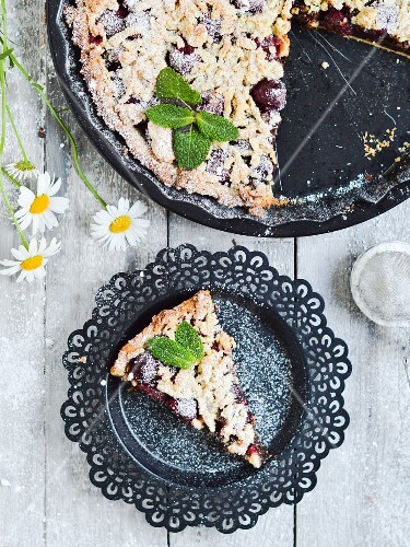 A sliced cherry & chocolate pie dusted with powdered sugar.