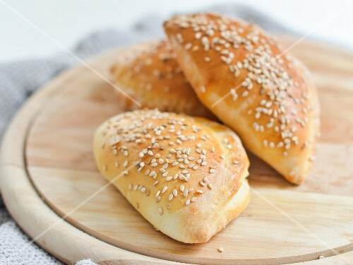 Dough stuffed with ham, cheese and pickles and sprinkled with sesame seeds