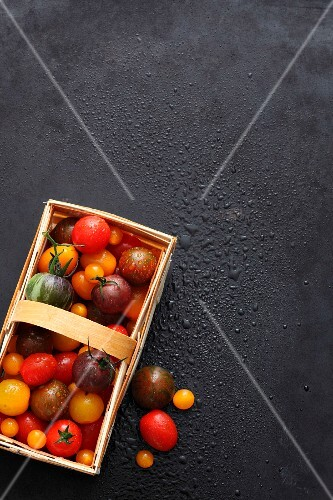 Various types of tomatoes in a wooden basket on a black surface