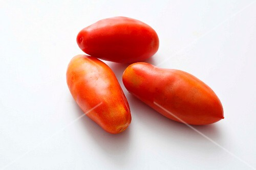 Three plum tomatoes on a white surface
