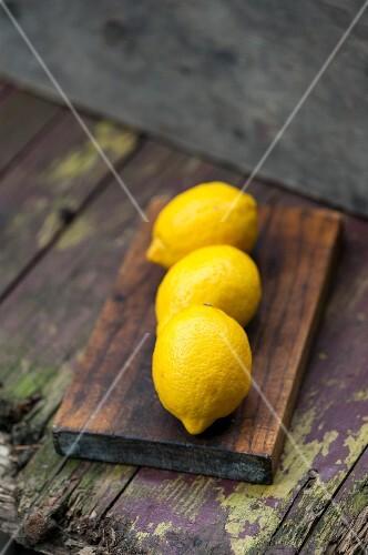 Three lemons on a wooden board