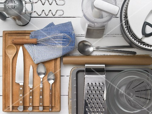 Kitche utensils: a handheld mixer with dough hooks, a chopper, a salad spinner, a measuring jug, a box grater, spoons, knives and a whisk