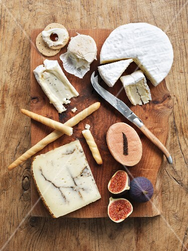 A cheeseboard with fresh figs, breadsticks and crackers (seen from above)