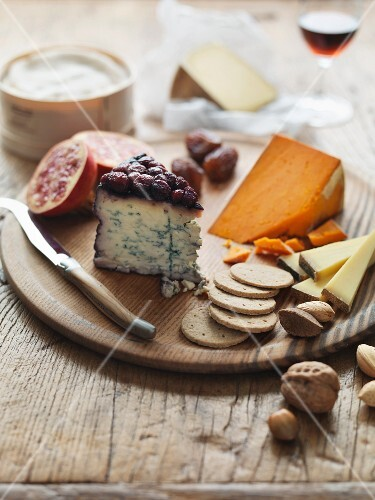 A cheeseboard with crackers, nuts and fruits