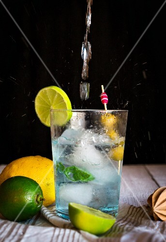 A gin and tonic garnished with olives and lime