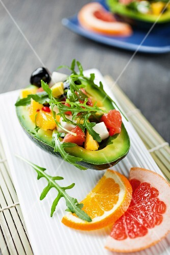 Avocado filled with a citrus fruit, mozzarella, olive and rocket salad
