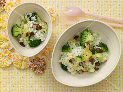 Potatoes in a creamy sauce with broccoli and pumpkin seeds