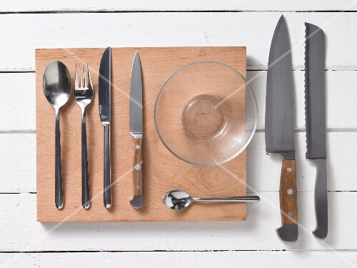 Assorted kitchen utensils: cutlery, kitchen knives and a glass bowl