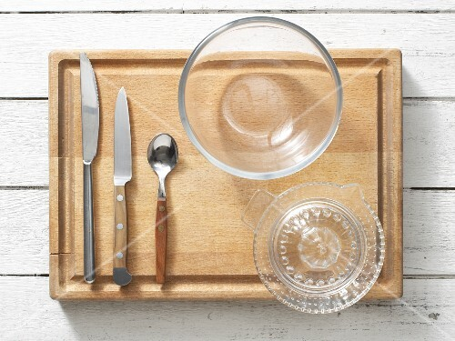 Kitchen utensils: cutlery, a citrus juicer and a glass bowl