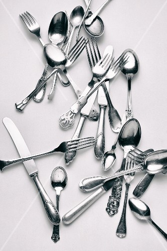 Various forks, knives and spoons on a white surface