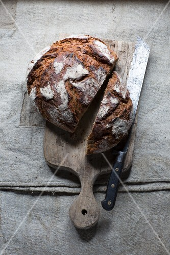 A loaf country bread on a wooden board