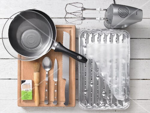 Assorted kitchen utensils, a grill tray, a hand mixer, a frying pan and cutlery