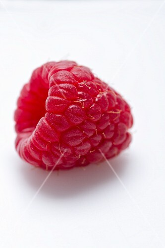 A raspberry on a white surface