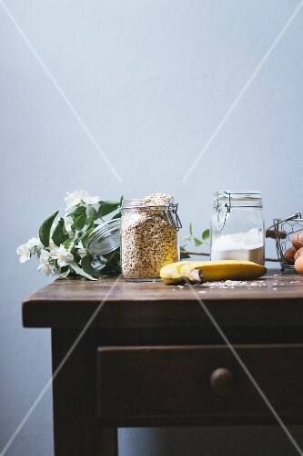 An arrangement of ingredients in storage jars, bananas and eggs on a table