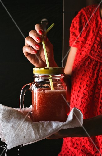 A woman holding a smoothie in a screw-top jar with a straw