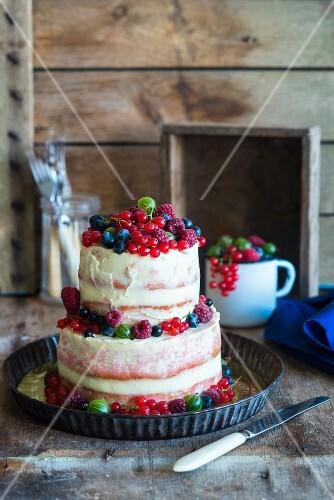 Zweistöckiger Semi-Naked Cake mit frischen Beeren