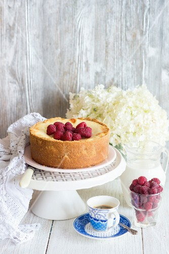 Vanilla cheesecake decorated with raspberries on a cake stand next to a cup of coffee
