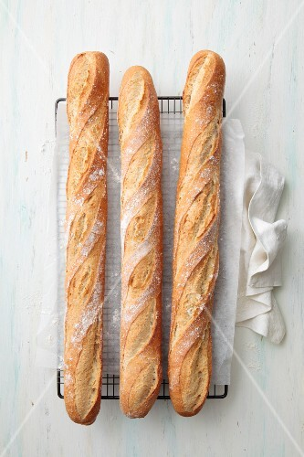 Three baguettes on a cooling rack