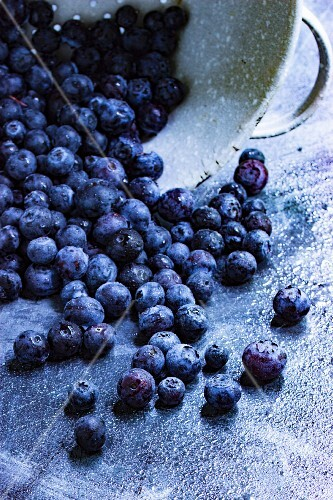 Fresh blueberries falling from a metal sieve