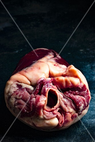 A close-up of a raw lamb heart against a dark background