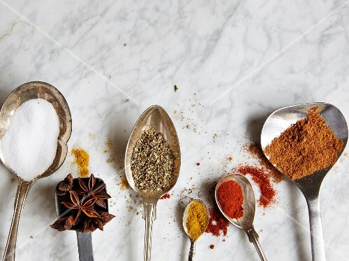 Spoons with assorted spices on a marble surface
