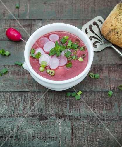 Beetroot soup with sliced radishes, fresh mint and spring onions