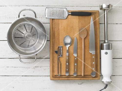 Assorted kitchen utensils: a saucepan, a measuring cup, a grater, cutlery and a hand liquidiser