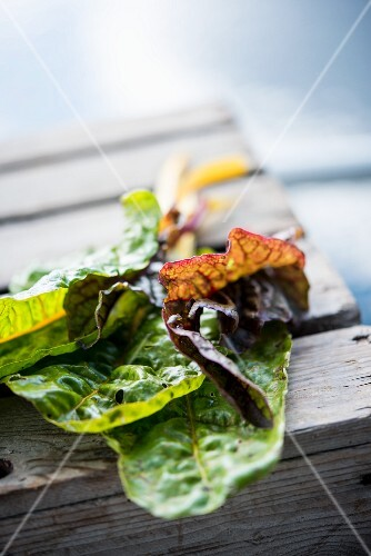Several leaves of chard on a wooden crate