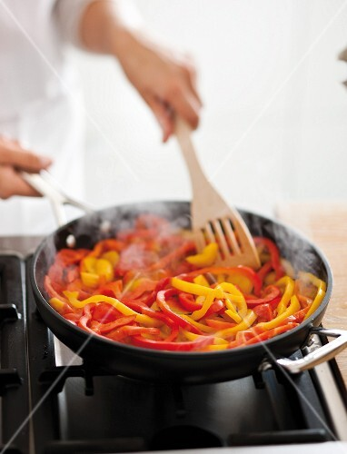 Red and yellow pepper strips being fried in a pan