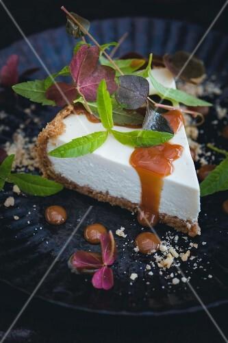 A slice of cheesecake with caramel sauce, lemon verbena and clover