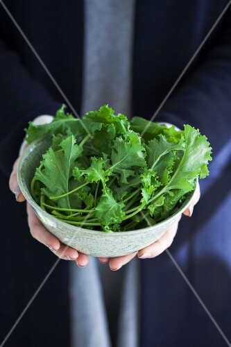 A person holding a bowl of fresh rapini