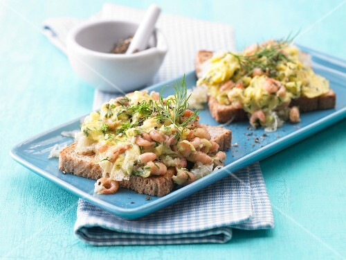Scrambled egg with shrimps on toast with dill and fennel